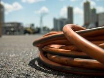 在地面上的橙色延长绳路在建造场所 免版税图库摄影