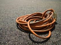 在地面上的橙色延长绳路在建造场所 图库摄影