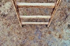 在地面上的老木梯子 免版税库存图片
