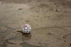 在地面上的老足球 免版税库存图片