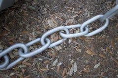 在地面上的金属链子 免版税库存照片