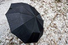 在地面上的黑大伞架在雪 免版税图库摄影