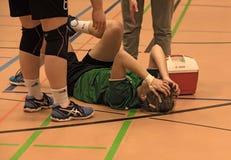 在地面上被伤害一名受伤的妇女的药物治疗 免版税库存照片