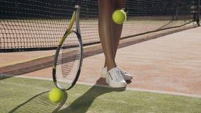 在地面和投掷的网球的女性网球员spining的球拍 影视素材