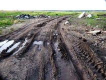 在地面泥泞的路的轮胎轨道 库存照片