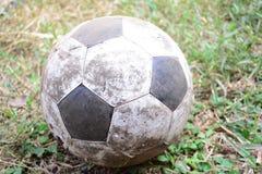 在地面的老橄榄球 库存图片