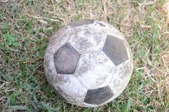 在地面的老橄榄球 库存照片