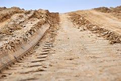在地面的轮子轨道 在泥泞的路的轮胎轨道 免版税库存图片