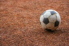 在地面的年迈的足球 免版税库存图片