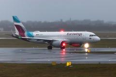 在地面的Eurowings飞机在杜塞尔多夫机场德国在雨中 免版税库存照片