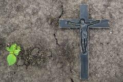 在地面背景的黑木耶稣受难象与一个绿色计划 免版税库存照片
