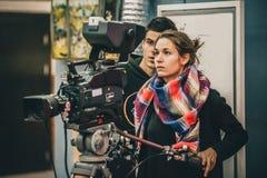 在场面之后 摄影师和助理与凸轮的射击影片 免版税图库摄影