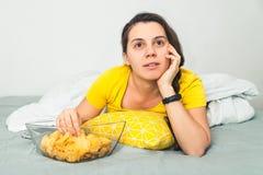 在坏手表电影的妇女谎言和吃snaks 免版税库存照片