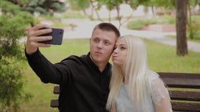 在坐一条长凳在城市公园和做selfie的爱的愉快的夫妇在电话 股票录像