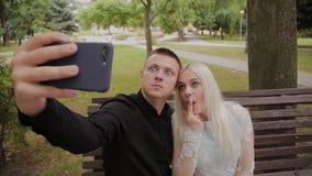 在坐一条长凳在城市公园和做selfie的爱的愉快的夫妇在电话 股票视频