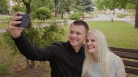 在坐一条长凳在城市公园和做selfie的爱的愉快的夫妇在电话 影视素材