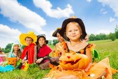 在坐万圣夜的服装的许多孩子紧密 免版税库存照片