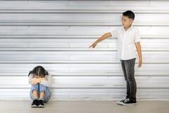 在坐亚裔女孩,在他们后的白色墙壁的亚洲男孩点 免版税库存照片