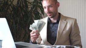 在坐他的工作场所和在手中拿着捆绑金钱的衣服的年轻愉快的商人 成功企业的人员 股票录像