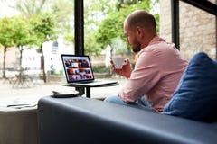 在坐在与大窗口的现代咖啡店的便携式计算机上的英俊的人工作 免版税库存照片