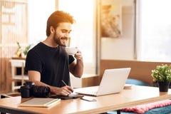 在坐在书桌的膝上型计算机的自由职业者有胡子的人饮用的咖啡 图库摄影