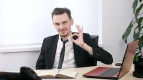 在坐在办公室和显示好标志的衣服的年轻商人 Loopable 股票视频