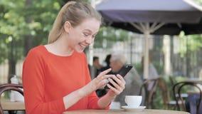 在坐在咖啡馆大阳台的智能手机的年轻女人欢呼的成功 影视素材