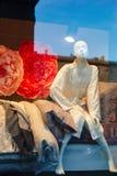 在坐在商店窗口显示的浴巾的时装模特 免版税库存照片