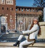 在坐在喷泉附近的Sforza城堡前面的旅游妇女 免版税库存照片