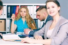 在坐在她的队前面的衣服的年轻女性商业领袖 严肃的企业和合作概念 免版税库存图片