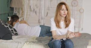 在坐在床上的关系的问题担心的哀伤的紧张的妇女,她的男朋友在转动附近说谎  股票视频