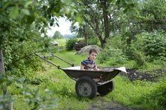 在坐在推车的庭院男孩的一个村庄 库存照片