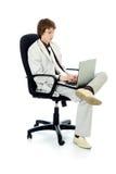 在坐在椅子和拿着膝上型计算机的衣服的英俊的年轻商人 图库摄影