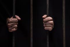 在坐在监狱的人的手上的特写镜头 库存照片
