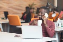 在坐在计算机的电话的非裔美国人的商人 库存照片