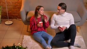 在坐地毯用茶和沟通在圣诞节家庭环境的观点的上面的快乐的白种人朋友下 股票录像