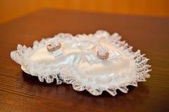 在坐垫的两只婚姻的金戒指 免版税图库摄影