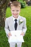 在坐垫的页男孩运载的婚戒 库存照片