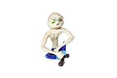 在坐姿的Umorik 一个皮包骨头的字符的小雕象与一个大头的 铸造从黏土和黏土 免版税库存图片