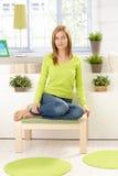 在坐年轻人的女孩绿色植物附近 免版税图库摄影