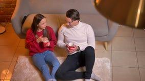 在坐有热的饮料的地毯和沟通在舒适家庭环境的观点的上面的快乐的白种人朋友下 影视素材