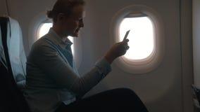 在坐椅子和使用流动终端的平面女孩客舱在电话和支付购买通过卡片 股票视频
