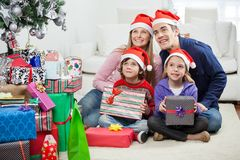 在坐由圣诞节礼物的圣诞老人帽子的家庭 免版税库存照片
