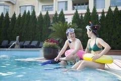 在坐由水池的边缘的潜航的齿轮的微笑的夫妇 免版税图库摄影