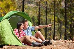 在坐的帐篷的野营的夫妇看看法 免版税库存图片
