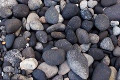 在坐骨岸,意大利的Vulcanic黑暗的圆的石头 库存图片