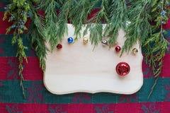在坚硬木背景的圣诞节铃声与绿色顶面框架 库存图片