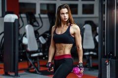 在坚硬锻炼以后的运动少妇在健身房 健身女孩拿着有嬉戏营养的振动器 免版税图库摄影