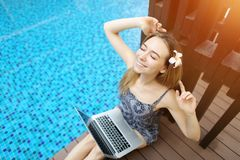 在坚苦工作以后的愉快的妇女休息在与膝上型计算机的游泳池,做舒展手 免版税库存照片