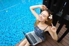 在坚苦工作以后的愉快的妇女休息在与膝上型计算机的游泳池, d 图库摄影